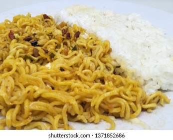 Close up fried instant noodle or mie mee goreng on plate, isolated on white background served with sprinkling of fried onions on top and rice. Typically indonesian people eat high calorie bad health