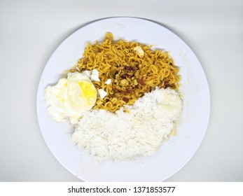 Close up fried instant noodle or mie mee goreng on plate, isolated on white background served with boiled egg, sprinkling of fried onions on top, and rice. Typically indonesian high calorie bad health