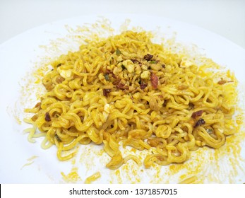 Close up fried instant noodle or mie mee goreng on plate, isolated on white background served on plate, sprinkling of fried onions on top with oily stain around
