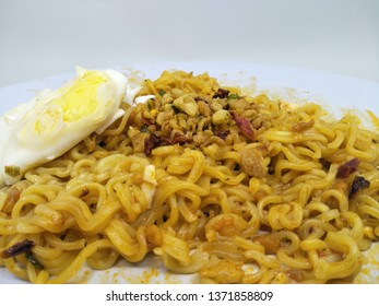 Close up fried instant noodle or mie mee goreng on plate, isolated on white background served with boiled egg, sprinkling of fried onions on top. Typically indonesian people eat. high calorie health