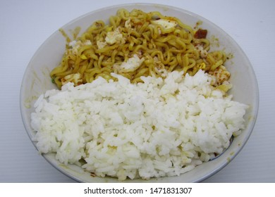 Close up fried instant noodle or mie mee goreng on plate, isolated on white background served with boiled egg, sprinkling fried onions on top, nasi rice. Typically indonesian high calorie bad health