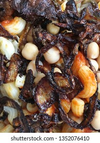 Close up of fried onions, macaroni, chickpeas and tomato sauce in a traditional koshari dish from Egypt