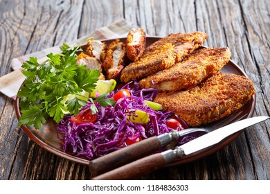 Close up of fried pork chops in breadcrumbs with vegetable salad, served on a clay plate with lime and parsley on a wooden table