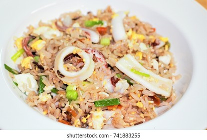 Close up fried rice with seafood on white plate.