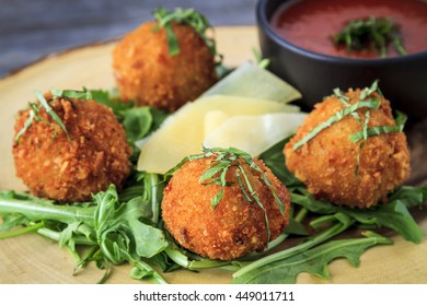 Close up of fried risotto balls sitting on bed of micro green with parmesan cheese garnish and marinara sauce for dipping