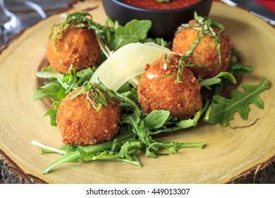 Close up of fried risotto balls sitting on bed of micro green with parmesan cheese garnish and marinara sauce