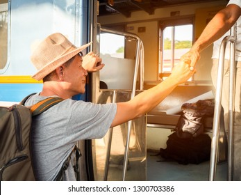 close up friend giving a helping hand to asia happy smailing backpacker man wear hat stepping up to a train.Handsome  passenger at train station.Travel concept.