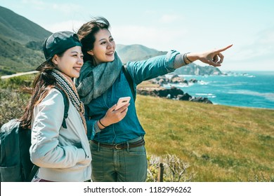close friends looking into the ocean and one girl pointing to somewhere with a phone held by a background of stunning coast.