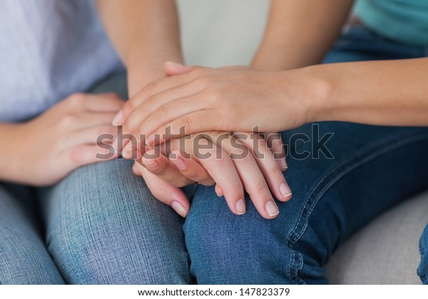 Close friends touching hands at home on the couch