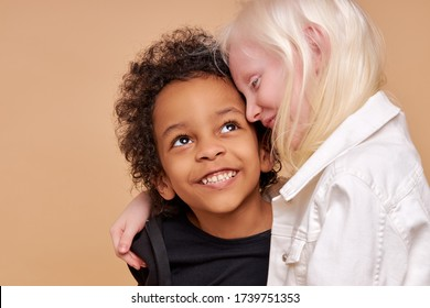 close friendship between two children of different nationalities, beautiful caucasian albino girl and african boy with curly hair, they are hugging