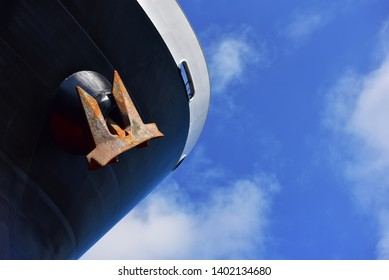 Close up Front boat or cargo ship under blue sky and anchor hanging forecastle deck.