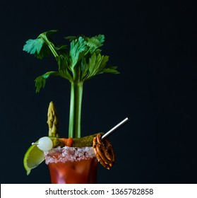 Close up front facing view of a Caesar cocktail otherwise known as Bloody Mary garnished with celery, pickles, pretzel and a lime ready for drinking.