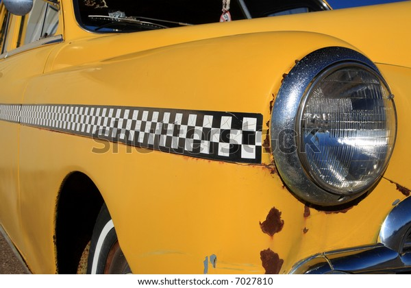 Close up of front fender and headlight of an 1950 automobile with checkered stripe found in New Mexico on Route 66