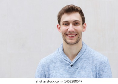 Close up front portrait of handsome young man smiling and looking at camera