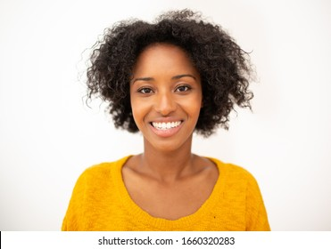 Close up front portrait smiling young african american woman with curly hair by isolated white background