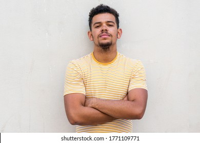Close up front portrait tough young mixed race man staring with arms crossed by white background