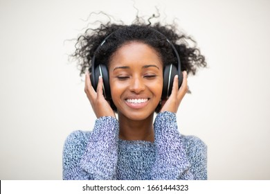 Close up front portrait young african american woman listening to music with headphones and eyes closed