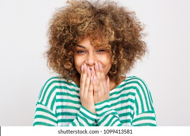 Close up front portrait of young woman laughing with hands covering mouth