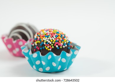 Close up front view of colorful chocolate cake ball in white background with empty space for text
