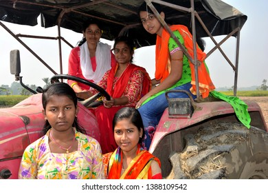 Close up front view of five young girls sitting on a tractor wearing colorful salwar kameez in a field, selective focusing