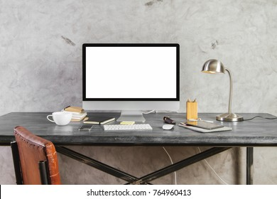 Close up and front view of hipster table with empty white computer screen, various other devices, coffee cup and objects on concrete wall background. Mock up