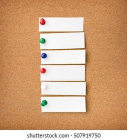 Close up front view of illustrative corkboard with blank white note cards pinned with colorful pins, on pinboard background.