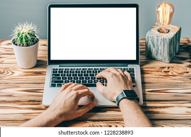 Close up front view of male hands working on laptop with blank white screen standing on wooden rustic desk. Grey wall on the background. Mock up, copy space for your text.
