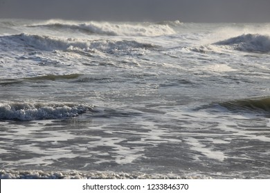Close up front view of the mediterranean sea during a sunny windy day. Pattern of white waves and splashes with sunlights. Symbol of movement. Abstract picture.