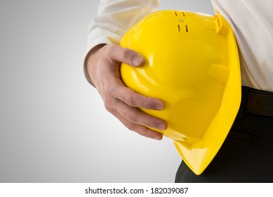 Close up front view of a professional man carrying a yellow hardhat against his hip conceptual of an architect, engineer, builder or contractor isolated on grey.