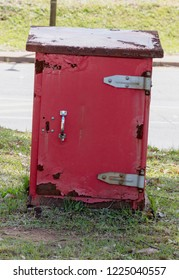 A Close up front view of a red old rusted post offcie post box storage unit