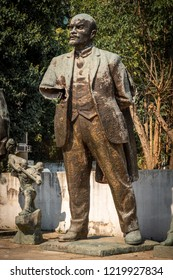 Close up front view of a worn broken bronze statue of Lenin in a city park in Tirana Albania.