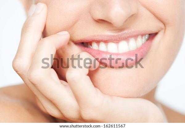 Nahaufnahme des frontalen Beauty-Sektion Porträt Blick auf eine junge Frau natürlichen Lächeln mit üppigen rosa Lippen auf ihrer Hand Lächeln mit weißen Zähnen, klassische Schönheit Details drinnen.