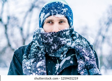 close up frost man's face with scarf covered by snow on a winter day