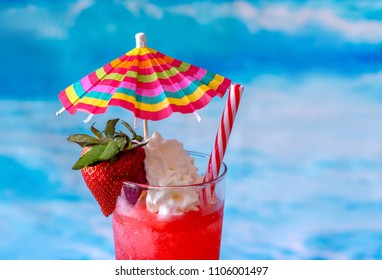 close up of a frosty frozen strawberry Daiquiri cocktail with a colorful umbrella and whipped cream