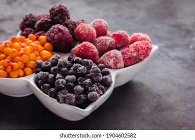 Close up of frozen mixed fruits and berries on a black table  Healthy food vitamins snack dessert