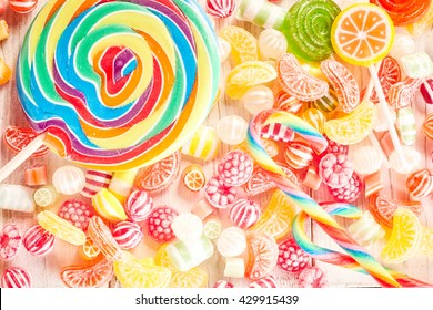 Close up of fruit flavored confections pile on table besides extra large swirl colored sucker and smaller lollipops