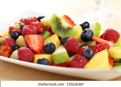 close up fruit salad strawberries kiwi pineapple and raspeberries on plate