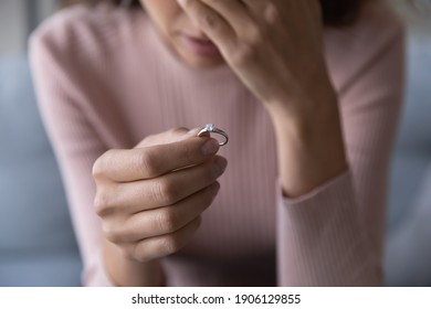 Close up frustrated millennial unhappy desperate woman holding engagement ring with diamond in hand, suffering from relations breakup or fiancee betrayal, denied marriage or getting divorced.