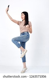 Close up full length size body photo of jump pretty charming she her girl hand holding telephone skype online internet in flight showing wear casual clothes white background