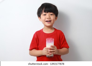 Close up fun portrait of cute little asian boy showing white milk mustache. Isolated against light background.