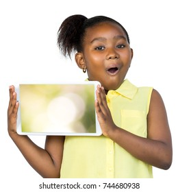 Close up fun portrait of cute little african girl with ponytail holding blank digital tablet. Kid with surprised facial expression isolated on white background.