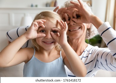 Close up funky old grandma small granddaughter with funny faces making binoculars with fingers like eyeglasses fooling around together at home. Eyesight check-up, eyewear store offer, have fun concept
