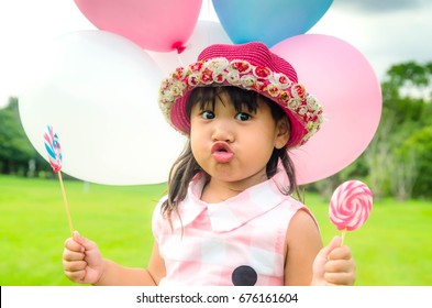 close up of  funny asian little girl portrait in pink dress plaid and lolipop candy and Balloon with blur park background.