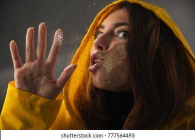 Close up of a funny girl dressed in raincoat with a hood on her head standing behind a wet with rain window and looking at camera isolated over gray background