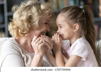 Close up of funny grand daughter joyful grandmother telling secrets each other gossiping sitting on sofa in living room at home, multi-generational family trusted relations, strong connections concept