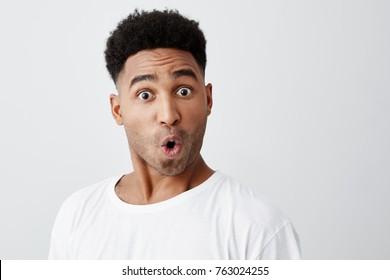 Close up of funny handsome young dark-skinned man with afro haircut in stylish white t-shirt looking in camera with raised eyebrows and surprised face expression.