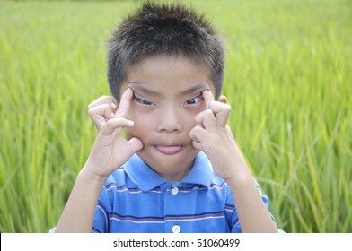 Close up Funny little boy against green rice fields