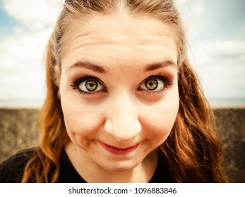 Close up of funny young teenage woman. Bizzare fish eye angle. Outdoor shot.