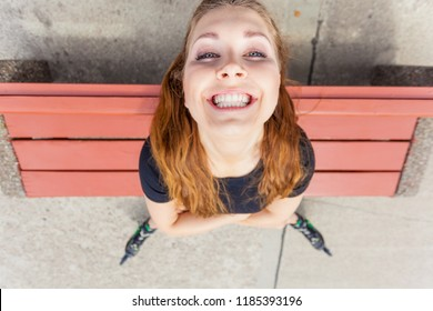 Close up of funny young teenage woman wearing rolling skates. Bizzare unusual angle. Outdoor shot.