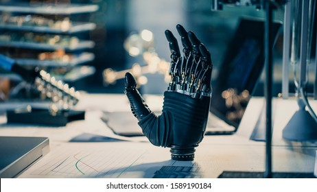 Close Up of a Futuristic Prosthetic Robot Arm Stands on a Desk in a High Tech Research Laboratory with Modern Computer Equipment.